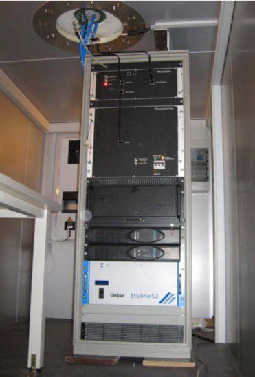 "Vertically pointing MIRA36-2009 mounted inside a trailer. The components are mounted in a 19"" rack. From top to bottom: Receiver, transmitter, PC including DSP, Console, UPS, Waveguide drying unit. The Antenna (not visible on this picture) is mounted on the trailer roof."