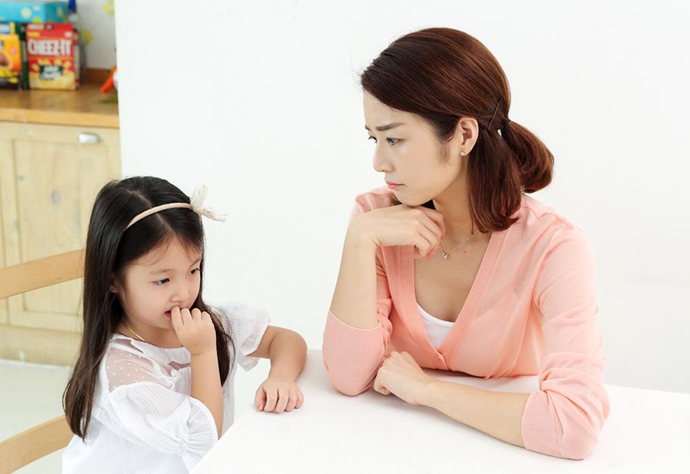 손톱 뜯는 아이와 아이를 바라보며 걱정하는 엄마