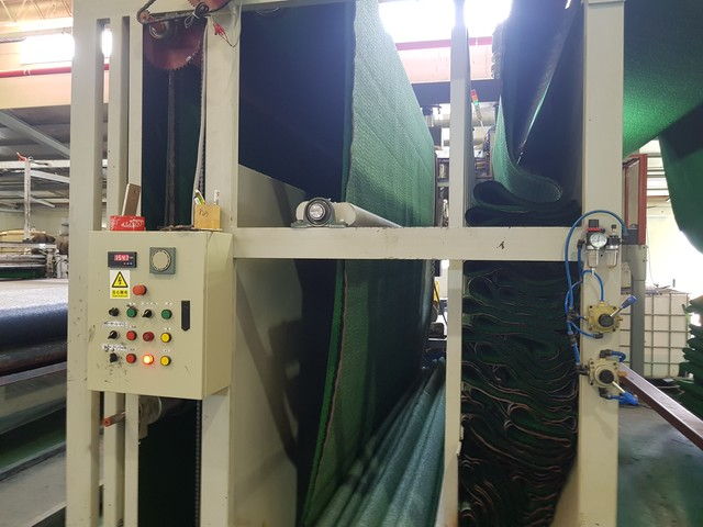 Putting the yarn layer into the backing line
