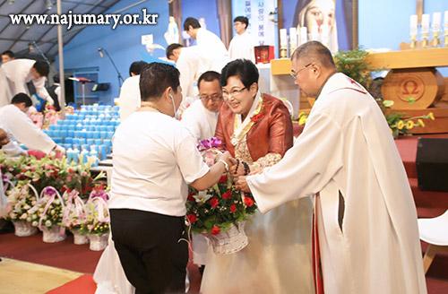 기도회 시작, 성모님 행렬 후 꽃과 초를 성모님상 앞에  봉헌하는 모습