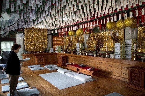 6관음전 안에서 기도하는 신도, 많은 신도들의 소원을 담은 연등이 6관음전 안에 가득하다.
