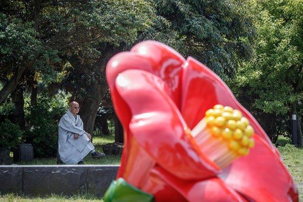 '평화의 길' 이사장인 명진 스님이 4.3 평화기념관 앞의 동백꽃 형상물 옆에서 생각에 잠겨있다.