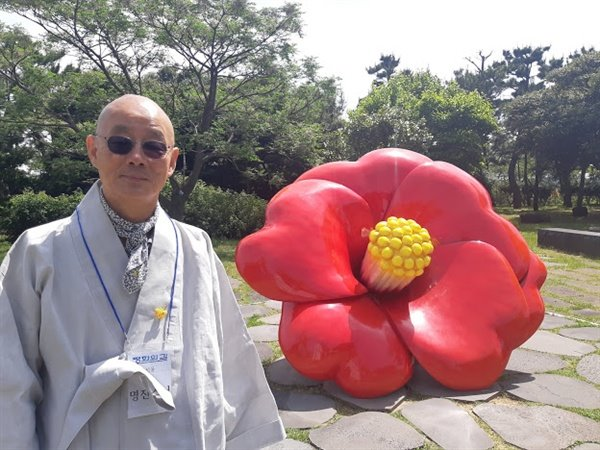 제주 4.3 평화공원에 있는 동백꽃 조형물 앞에 선 명진 스님.