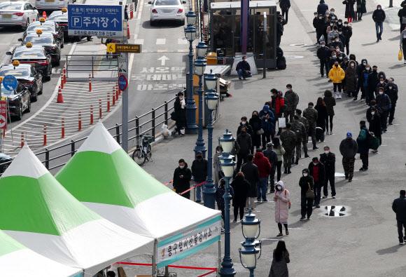 15일 오후 서울역에 마련된 코로나19 임시 선별검사소를 찾은 시민들이 길게 줄을 서 있다. 2021.2.15 연합뉴스