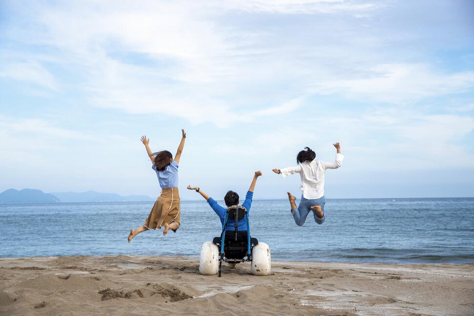 무빙트립 신현오 대표(가운데)가 비포장도로용 휠체어를 타고 바다를 즐기고 있다.