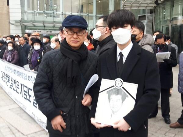 17일 오전 서울 광화문 동아일보사 앞에서 열린 '3·17 대량해직 규탄 45주년 기자회견'에서 이부영 자유언론실천재단 이사장(왼쪽)이 고 권근술 동아투위 위원의 영정을 들고 참가한 손주 권민수(오른쪽)씨와 함께 했다. 사진 동아투위 제공