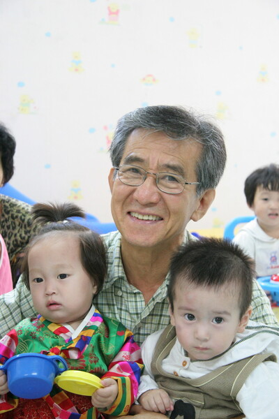 어린이어깨동무의 지원으로 2004년 건립한 '평양어깨동무어린이병원'을 방문했을 때 입원한 북녘 어린이들을 안아주고 있는 생전의 권근술 이사장. 어린이어깨동무 제공