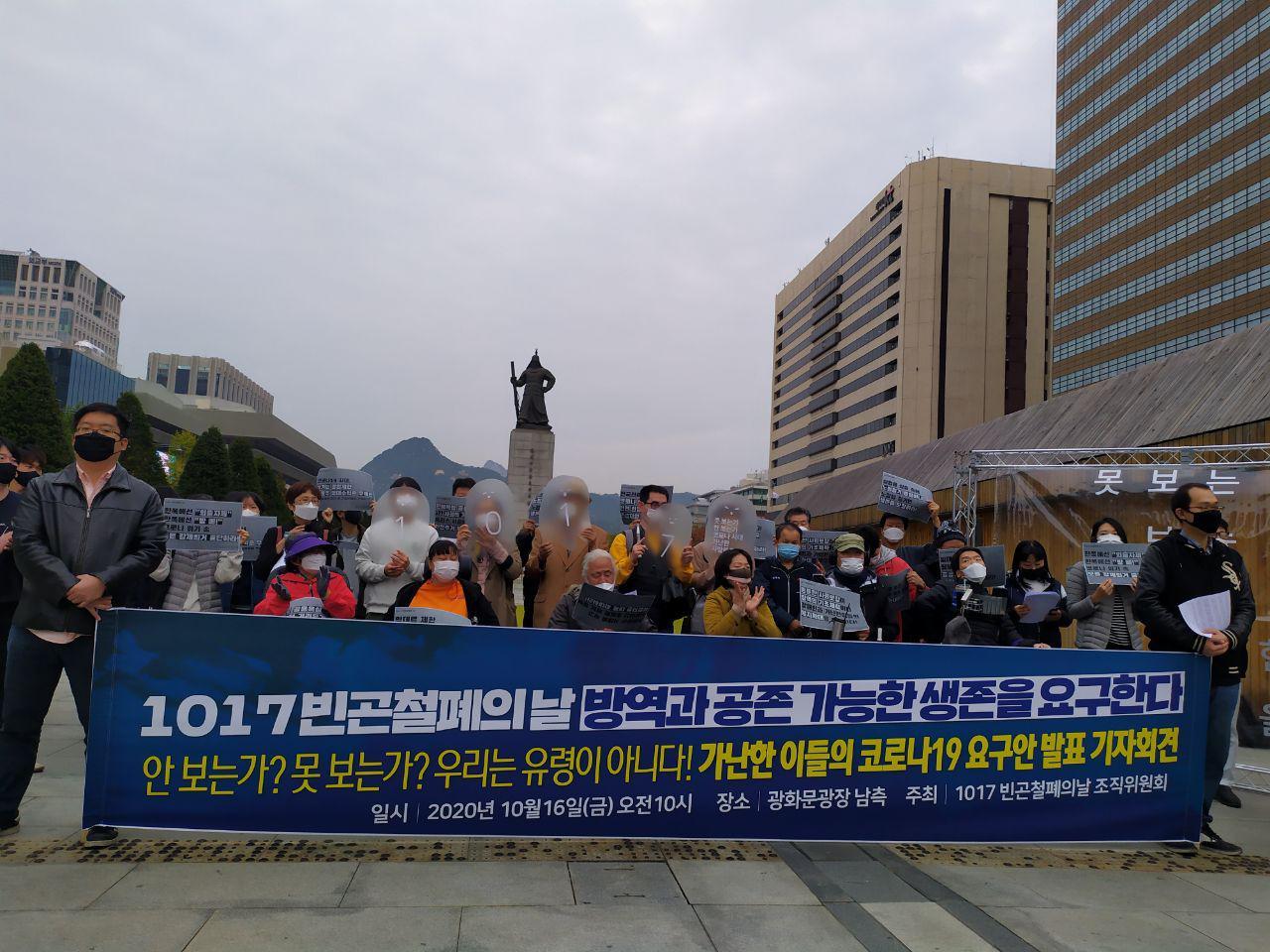 '1017 빈곤철폐의날 방역과 공존 가능한 생존을 요구한다'는 현수막을 들고 광화문 광장에서 약 20명의 사람들이 기자회견을 진행중이다.