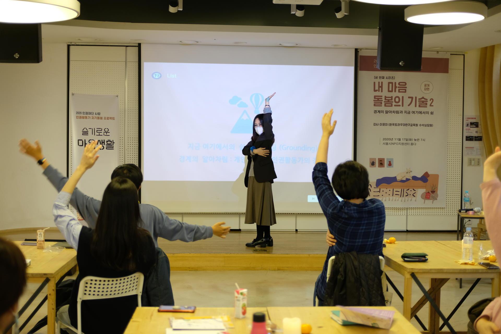 강사님이 앞에서 한쪽팔을 높이 들고 다른쪽팔로 몸통을 감싸고 있고, 참여자들은 따라하고 있음