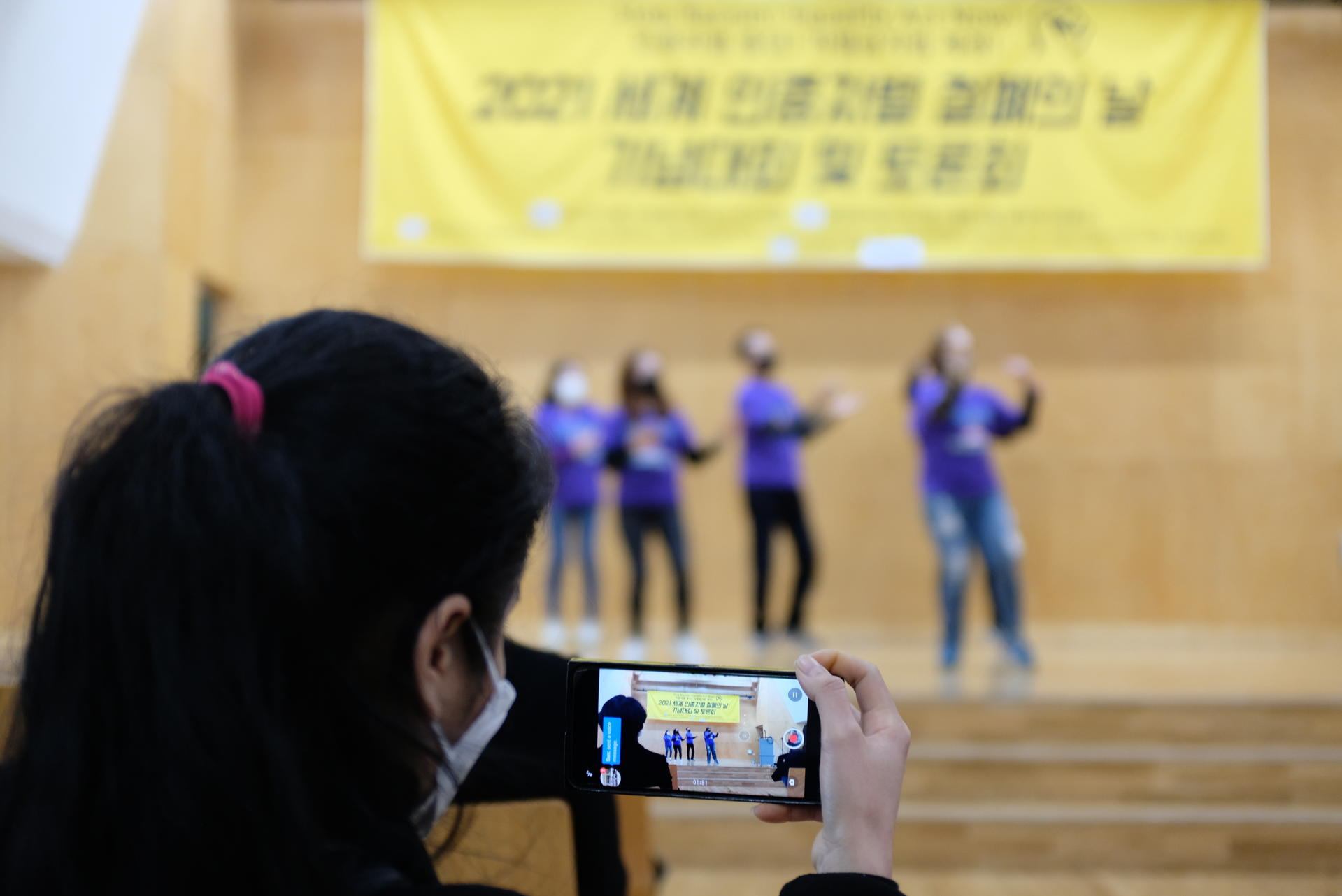 무대위 공연을 관객석의 참여자가 핸드폰으로 촬영하고 있다