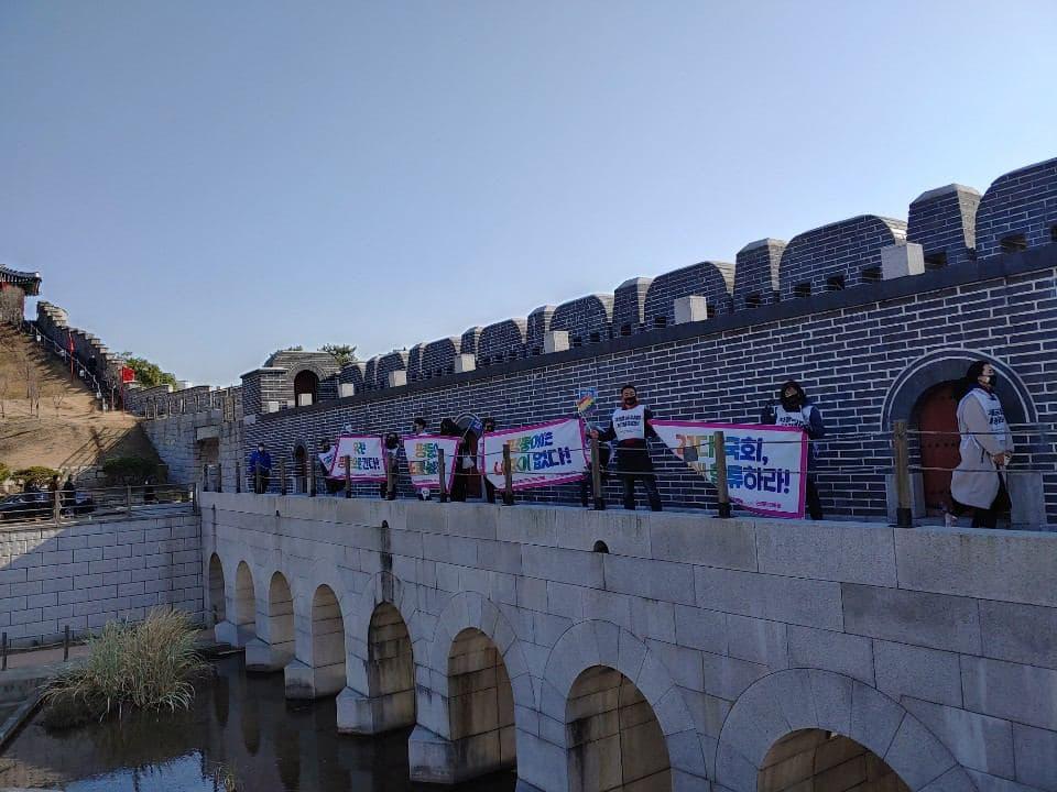 화성행궁 안에 성벽 앞에서 차별금지법 제정을 촉구하는 피켓을 들고 있는 다수의 사람들이 일열로 서있다.