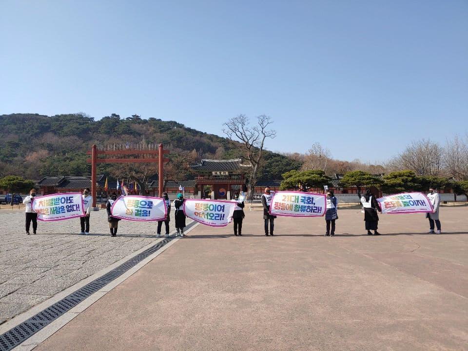 화성행궁 앞에서 다양한 피켓을 든 다수의 사람들이 일열로 서있다.