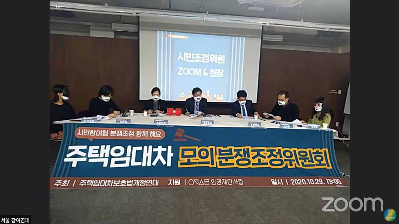 주택임대차 모의분쟁조정위원회가 적힌 현수막 뒤로 테이블이 있다. 테이블에는 7명이 앉아서 모의분쟁을 진행하고 있다.