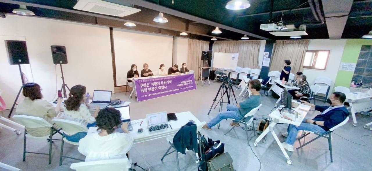 5명의 활동가가 보고회를 진행하고 있고, 7명의 사람들이 보고회를 지켜보고 있다. 일부는 카메라로 보고회를 촬영중이다.