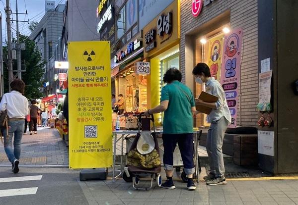 지난주 <송파구 방사능 안전 급식 조례> 서명에 한 주민이 참여하고 있다.